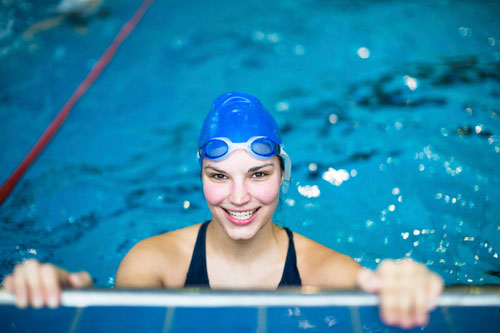 A woman swimming in a pool endangering her oral health!