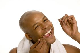 A man flossing his teeth with dental floss.
